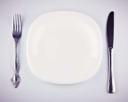 empty white dish knife and fork on grey background photo
