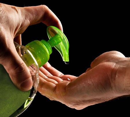 washing hands with liquid soap isolated on black photo