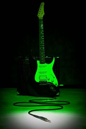 stratocaster: guitar and plug in spot of light, black background