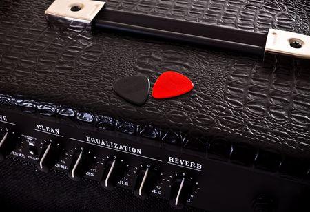 two plectrums on black guitar amplifier photo
