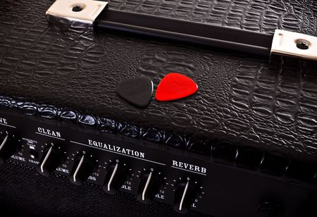 reverb: two plectrums on black guitar amplifier