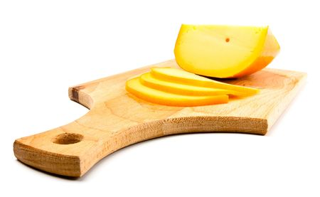 cheese slices on cutting board isolated on white photo