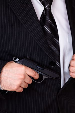man drawing his gun from jacket pocket closeup photo