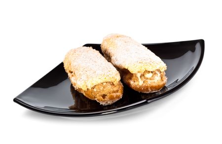 two eclairs on black dish isolated on white background photo