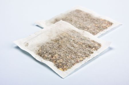 herbal tea bags laying on table, blue background photo