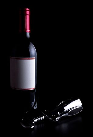 bottle of wine and corkscrew isolated on black background photo