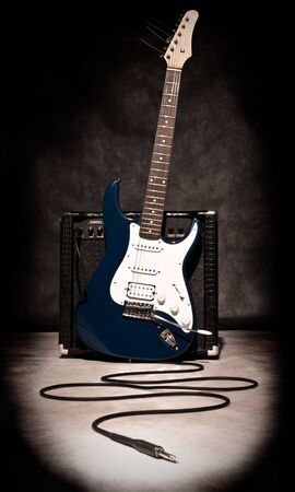 electric guitar and amplifier on dark background, sepia toned photo