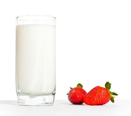 glass of milk: glass of milk and two strawberries on table