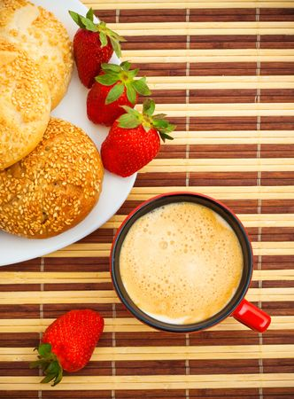 coffee, buns and strawberries on table, top view