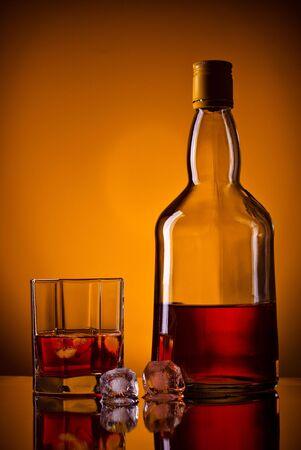 whiskey bottle, ice and glass, orange background photo