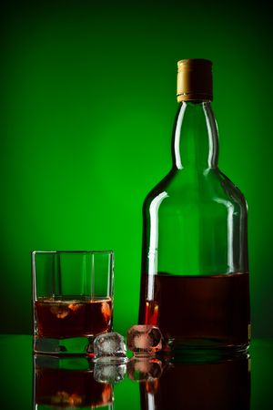 whiskey bottle, ice and glass, green background photo