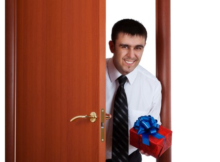 smiling young man with gift opening the door