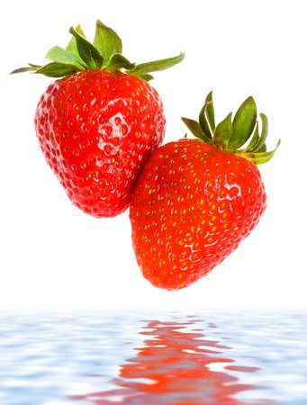 fresh ripe strawberries falling in water, white background photo