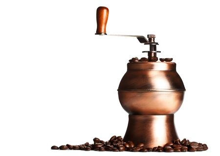 vintage coffee grinder standing on beans, white background