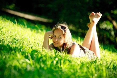 beautiful girl laying in grass on sunny meadow Stock Photo