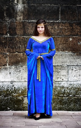 medieval woman stand against the stone wall photo