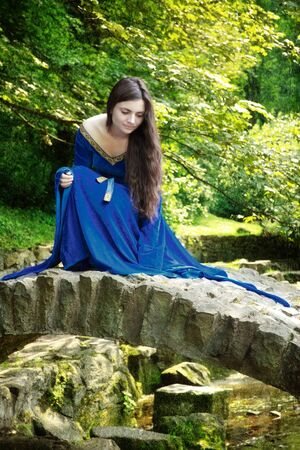 queen blue: medieval princess on stone bridge at summer