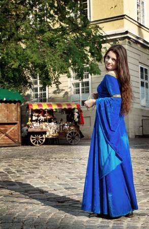 middeleeuwse jurk: middeleeuwse meisje op de straat van de oude stad  Stockfoto