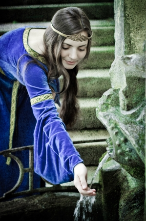 stone age: medieval girl next ancient spring, textured Stock Photo