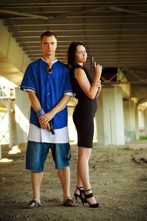 young couple with guns under bridge photo