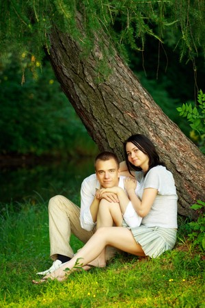 young couple sitting under fir tree photo