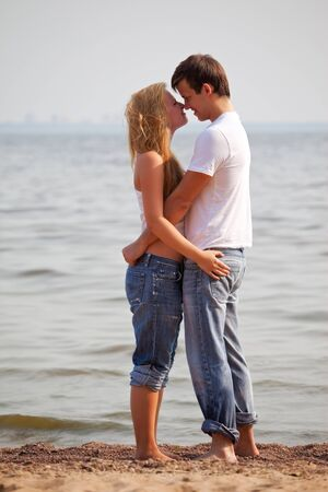 young couple embrace on a sunny beach photo