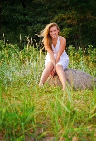 pretty woman in white dress sitting on big stone Stock Photo - 7622018