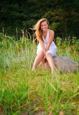pretty woman in white dress sitting on big stone photo