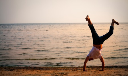 man doing handstand on sunset beach Stock Photo