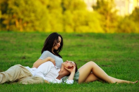 fondling: young couple laying on park lawn
