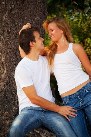 embraces: smiling couple next pine tree