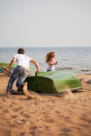 young couple fun and run around old boat on a beach Stock Photo - 7662171