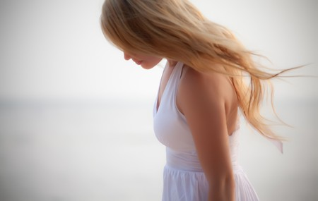 woman blowing: beautiful girl on seashore, soft focus