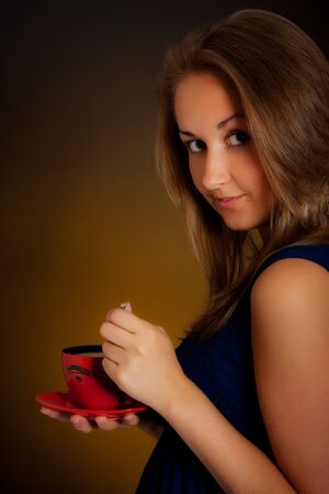 beautiful girl with cup of coffee, yellow background Stock Photo - 7662175