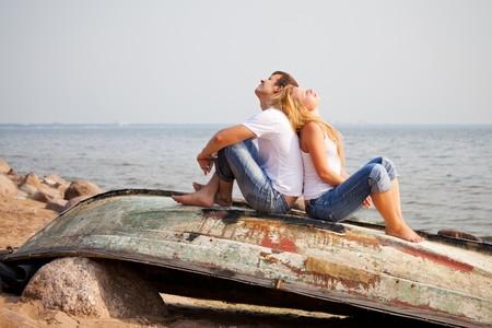 couple sitting on old boat back to back photo