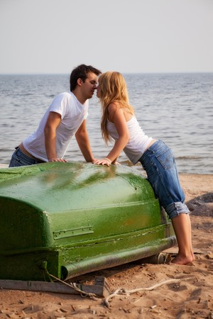 beautiful couple kissing on a beach near old boat photo