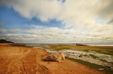 slob: seashore with big stone under clouds