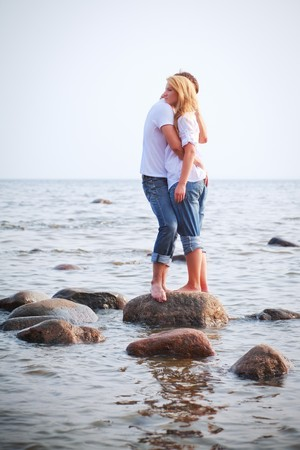 couple embrace on a big stone in sea photo