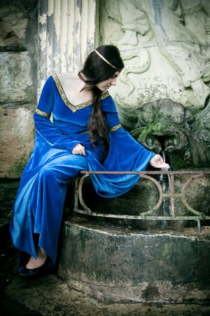 medieval girl next ancient spring photo