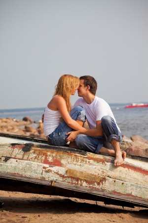 young couple sitting on old boat and kiss