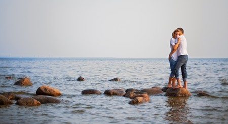 beautiful couple embrace on a stone in sea photo