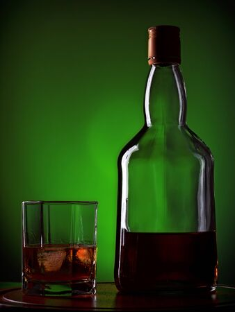whiskey and glass on wooden tray, green background photo