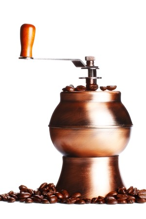 vintage coffee grinder standing on beans, white background photo