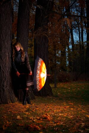 girl with umbrella in autumn park at evening Stock Photo - 8338855