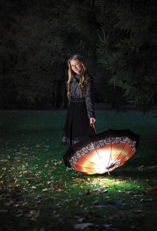 girl with umbrella in autumn park at evening photo