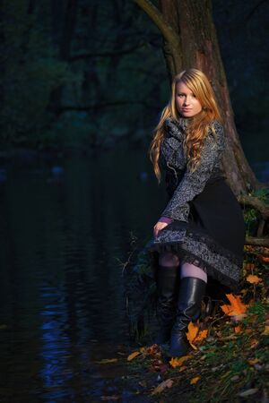 girl sitting on the edge of pond at evening photo
