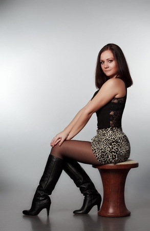 beautiful girl sitting on chair, gray background photo