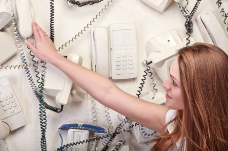 woman touching vintage phone on wall photo