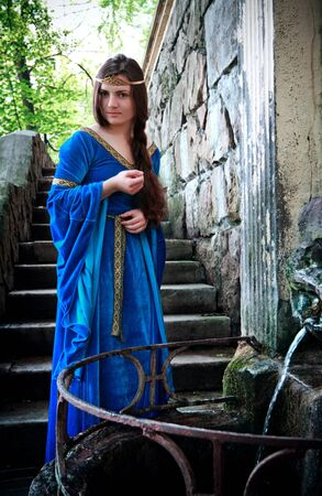medieval beautiful girl standing next ancient spring photo
