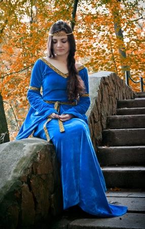 medieval dress: elf hermosa Princesa sentado en la escalera de piedra Foto de archivo